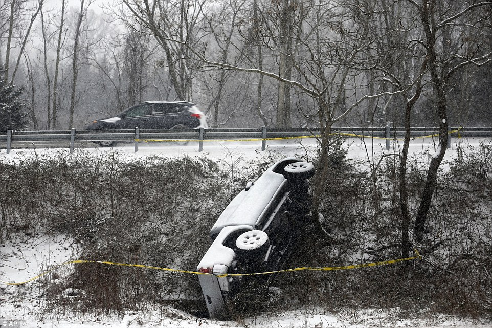 An overturned vehicle lies unattended in the median along Monacan Trail Road south of Charlottesville, Virginia, as snow falls on Friday