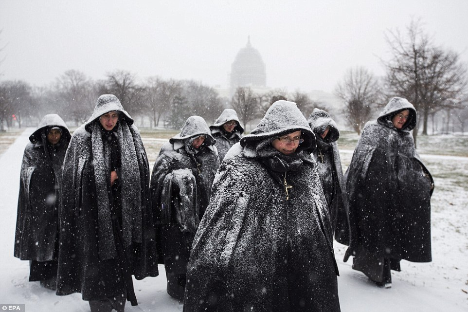 A group of nuns visiting Washington, DC from their convent in Chicago walk in the early snow outside the U.S. Capitol on January 22, 2016